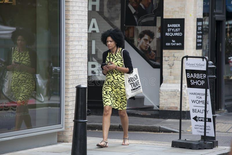 Fille afro-américaine concentrée avec le téléphone bouclé à disposition rapidement photo stock