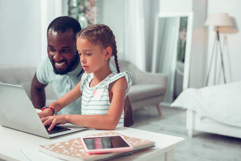 Fille afro-américaine focalisée avec des tresses dactylographiant sur un clavier d'ordinateur portable photographie stock libre de droits