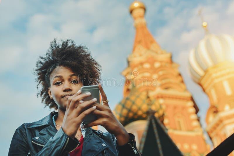 Fille Afro bouclée avec le smartphone sur la place rouge images stock