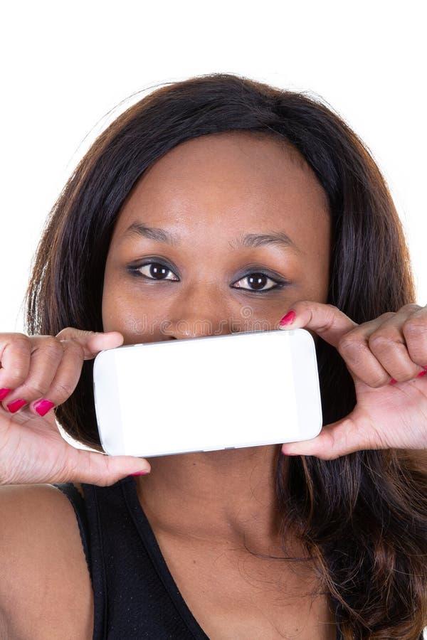Fille Afro de sourire montrant le téléphone portable d'écran vide au-dessus de ses lèvres de bouche de visage image libre de droits
