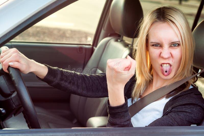 Fille agressive d'étudiant conduisant la voiture, image stock
