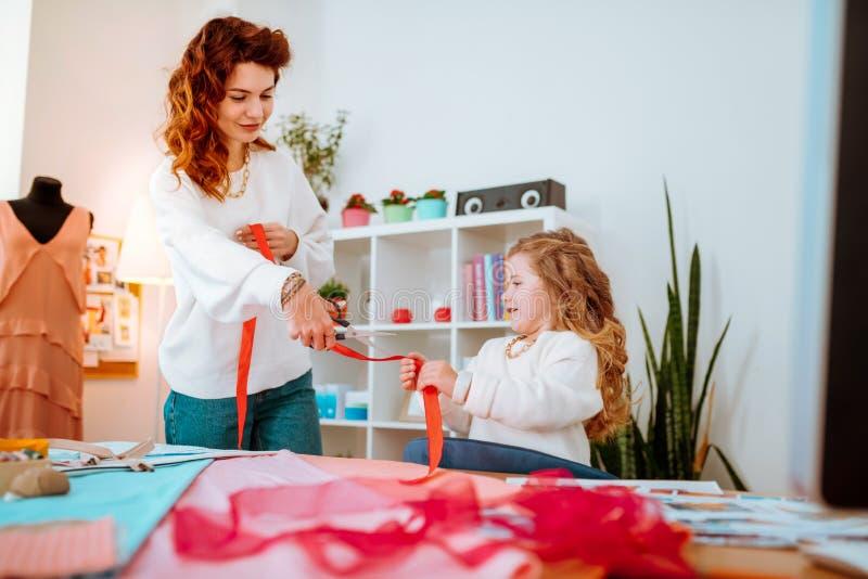 Fille aidant sa maman concevant des vêtements et coupant le ruban image stock