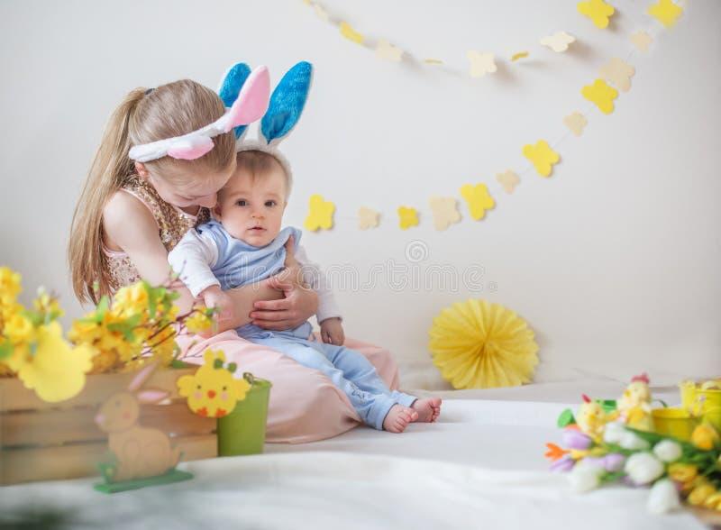 Fille aimante et ses oreilles de port de lapin de petit frère en décor de Pâques images libres de droits