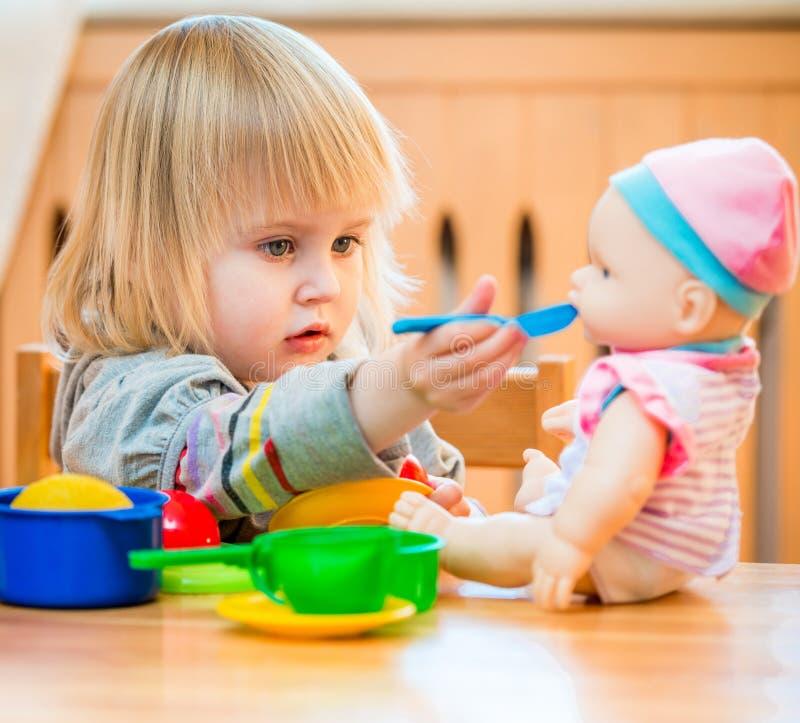 Fille alimentant une poupée photos stock