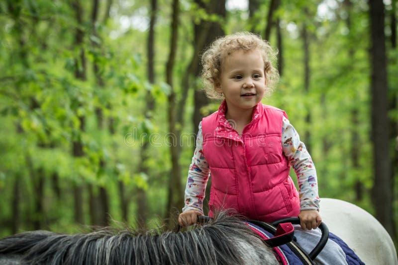 Fille appréciant l'équitation dans les bois, jeune jolie fille avec les cheveux bouclés blonds sur un cheval avec les feuilles ré images stock
