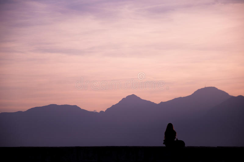 Fille appréciant le coucher du soleil photographie stock libre de droits
