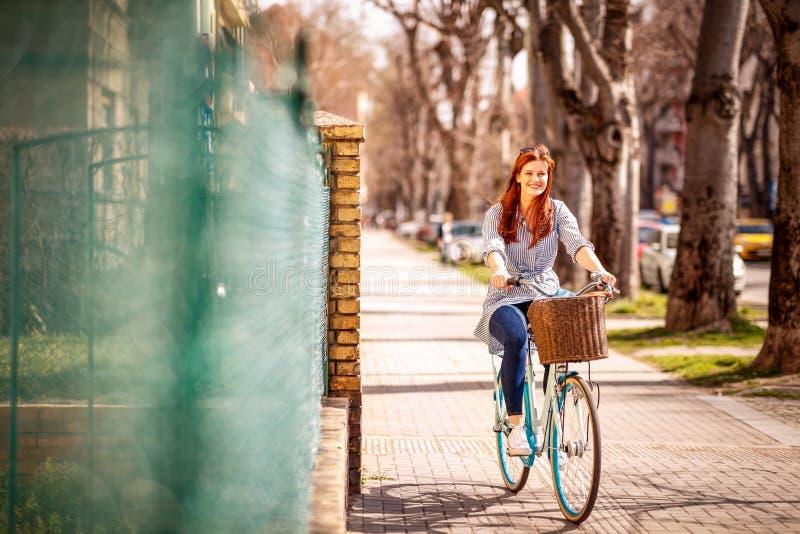 Fille appréciant le temps sur monter un vélo pendant la journée de printemps dans le CIT images stock