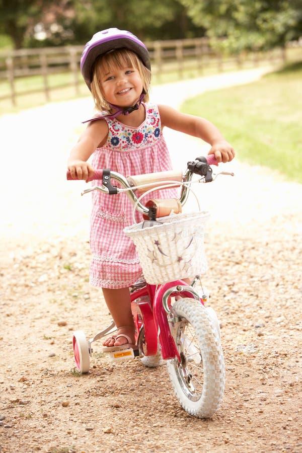 Fille apprenant à conduire le casque de sécurité s'usant de vélo photos stock