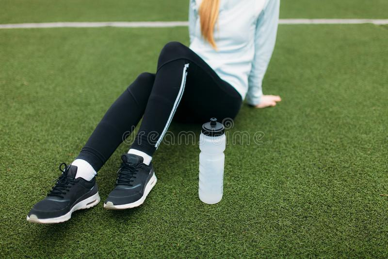 Fille après exercice, eau potable sur le terrain de football Portrait de belle fille dans les vêtements de sport photographie stock
