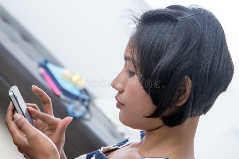 Fille asiatique à l'aide d'un téléphone intelligent images stock
