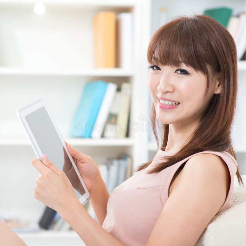 Fille asiatique à l'aide du PC de tablette photographie stock libre de droits
