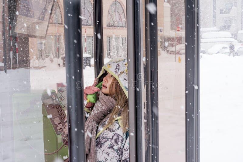 Fille asiatique à l'aide du téléphone public dans la neige photo stock