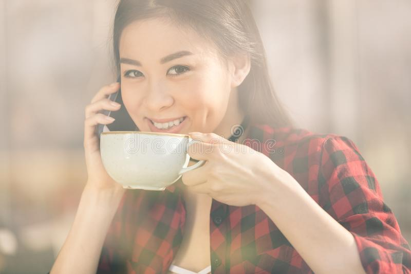 fille asiatique attirante à l'aide du smartphone et buvant du café en café de café images libres de droits
