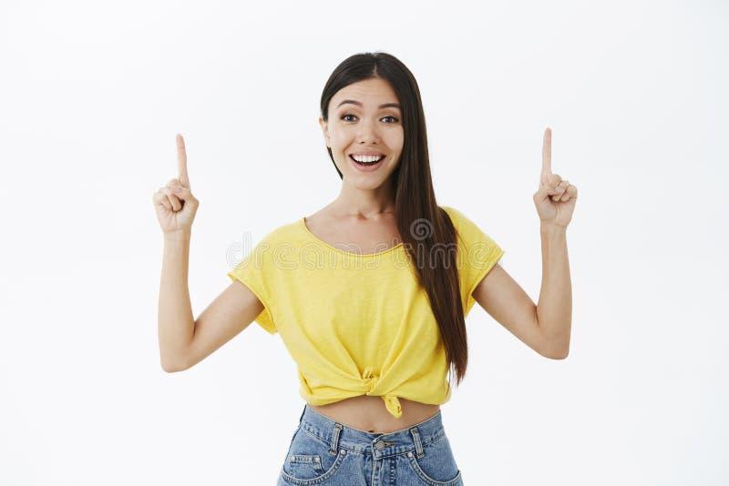 Fille asiatique attirante amusée sortante et amicale avec les cheveux foncés dans le T-shirt jaune soulevant des index se dirigea images libres de droits