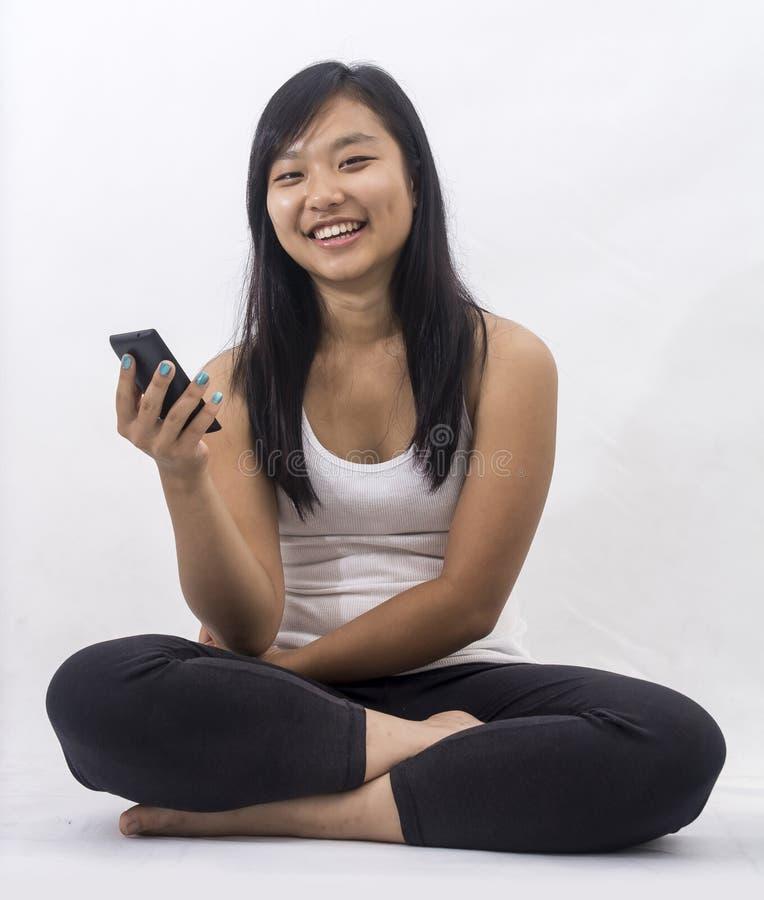 Fille asiatique avec un téléphone intelligent photo stock