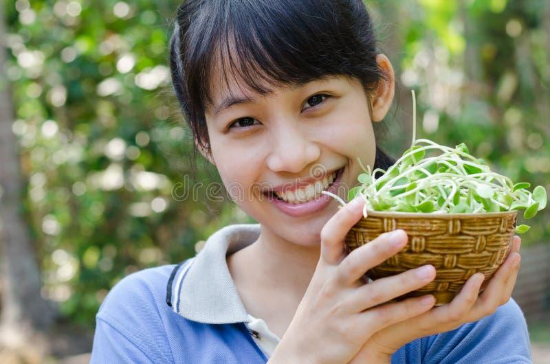 Fille asiatique d'adolescent heureuse avec les pousses végétales de tournesol image libre de droits