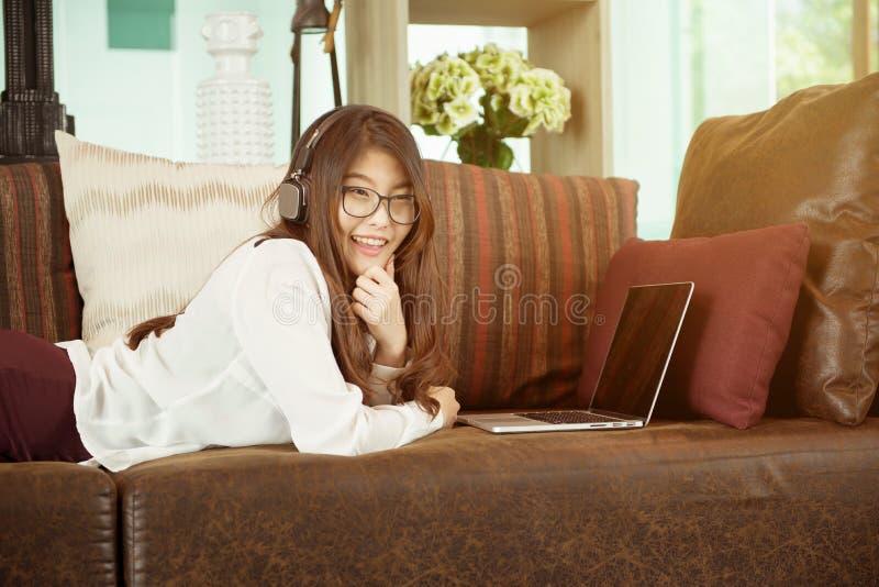 Fille asiatique d'affaires se penchant et à l'aide d'un ordinateur portable sur le sofa, personne images stock