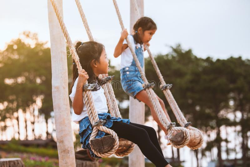 Fille asiatique d'enfant ayant l'amusement à jouer sur les oscillations en bois avec sa soeur dans le terrain de jeu avec la bell photo libre de droits