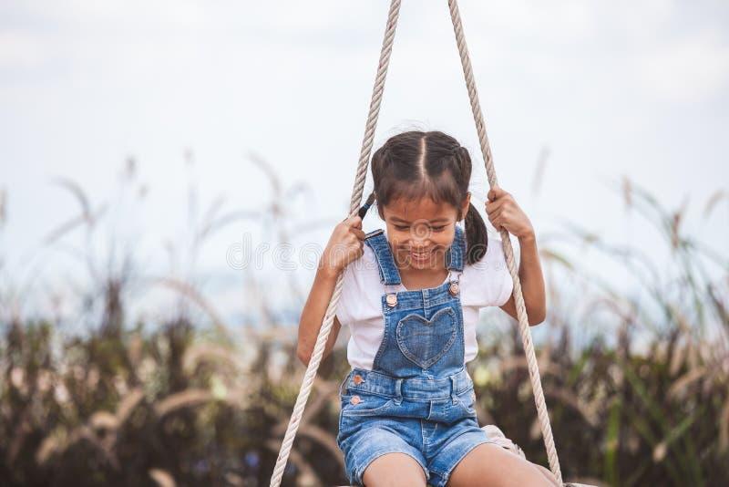 Fille asiatique d'enfant ayant l'amusement à jouer sur les oscillations en bois dans le terrain de jeu avec la belle nature image stock