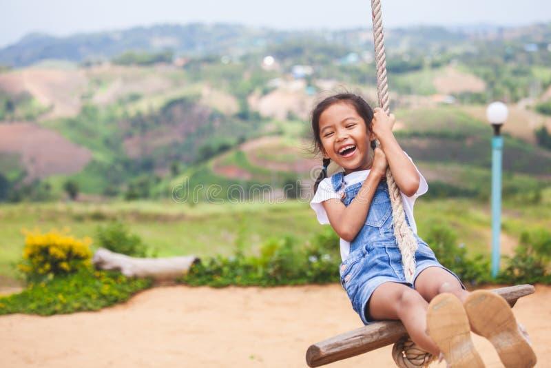 Fille asiatique d'enfant ayant l'amusement à jouer sur les oscillations en bois dans le terrain de jeu avec la belle nature photographie stock libre de droits
