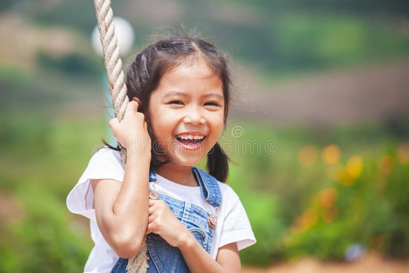 Fille asiatique d'enfant ayant l'amusement à jouer sur les oscillations en bois dans le terrain de jeu avec la belle nature photos stock