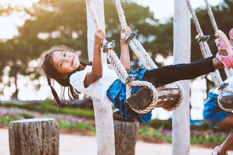 Fille asiatique d'enfant ayant l'amusement à jouer sur les oscillations en bois dans le terrain de jeu avec la belle nature photo stock
