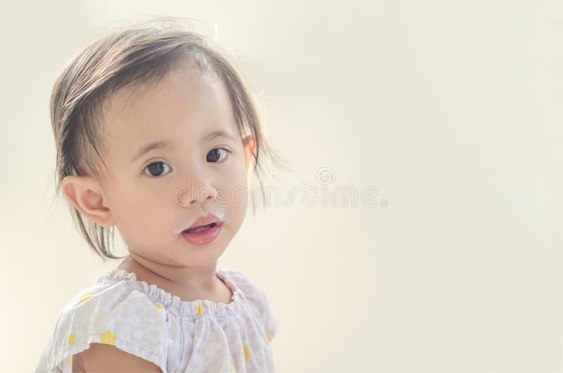 Fille asiatique d'enfant en bas âge avec la bouche sale du lait image libre de droits