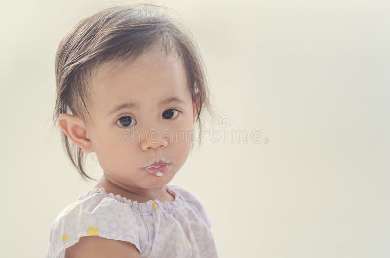 Fille asiatique d'enfant en bas âge avec la bouche sale du lait photos libres de droits