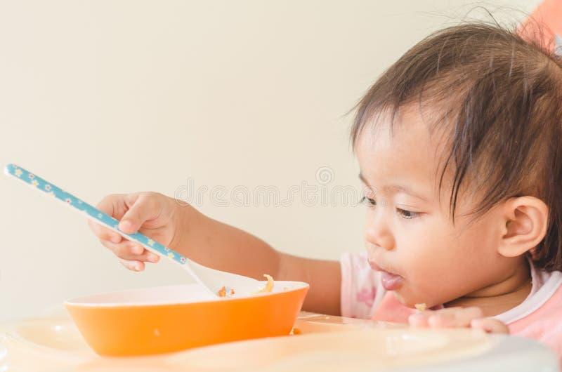Fille asiatique d'enfant en bas âge mangeant des céréales avec du lait sur la chaise d'arbitre au hom image stock