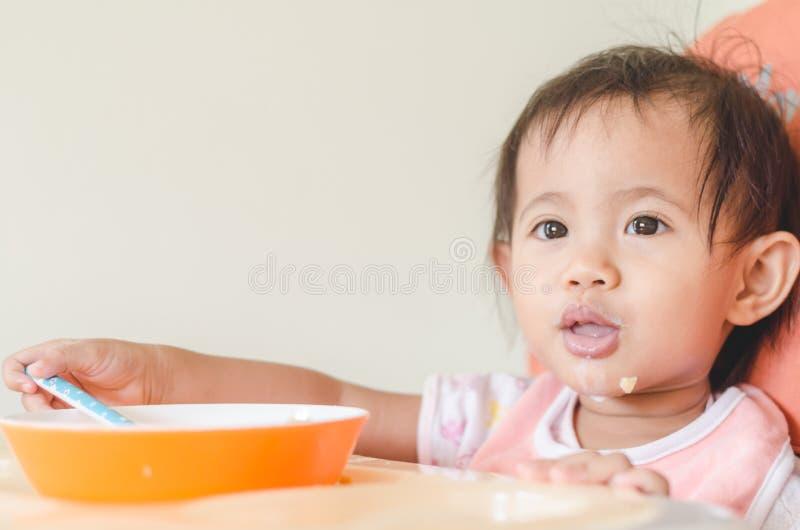 Fille asiatique d'enfant en bas âge mangeant des céréales avec du lait sur la chaise d'arbitre au hom photos stock