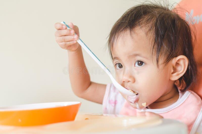 Fille asiatique d'enfant en bas âge mangeant des céréales avec du lait sur la chaise d'arbitre au hom images stock