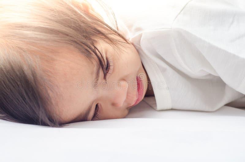 Fille asiatique d'enfant en bas âge se trouvant sur le lit à la maison photos stock