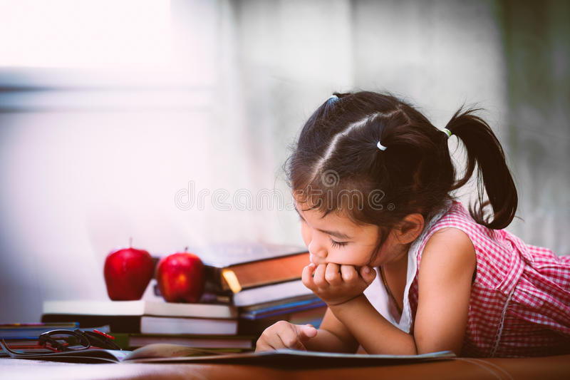 Fille asiatique d'enfant la petite s'ennuie pour lire un livre images libres de droits