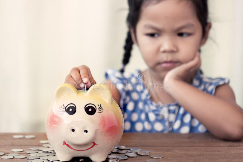 Fille asiatique d'enfant petite mettant la pièce de monnaie dans la tirelire photographie stock