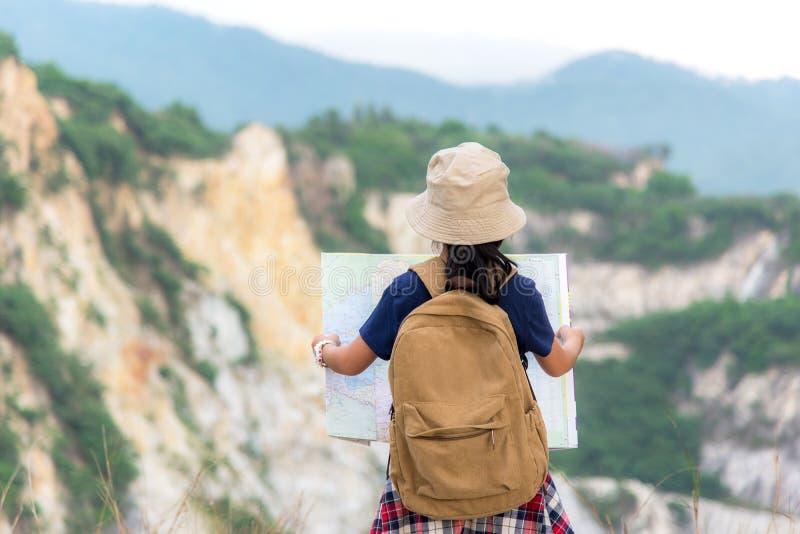 Fille asiatique d'enfants jugeant des cartes et des sacs à dos de voyage se tenant dans la montagne photos libres de droits