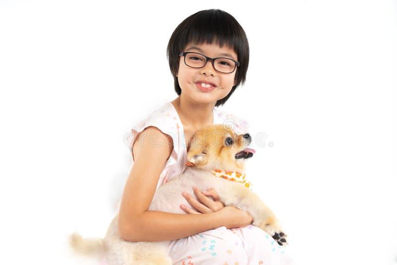 Fille asiatique d'isolement de portrait petite tenant le chien de Pomeranian avec soin sur le fond blanc Studio tir? de la fille  image stock
