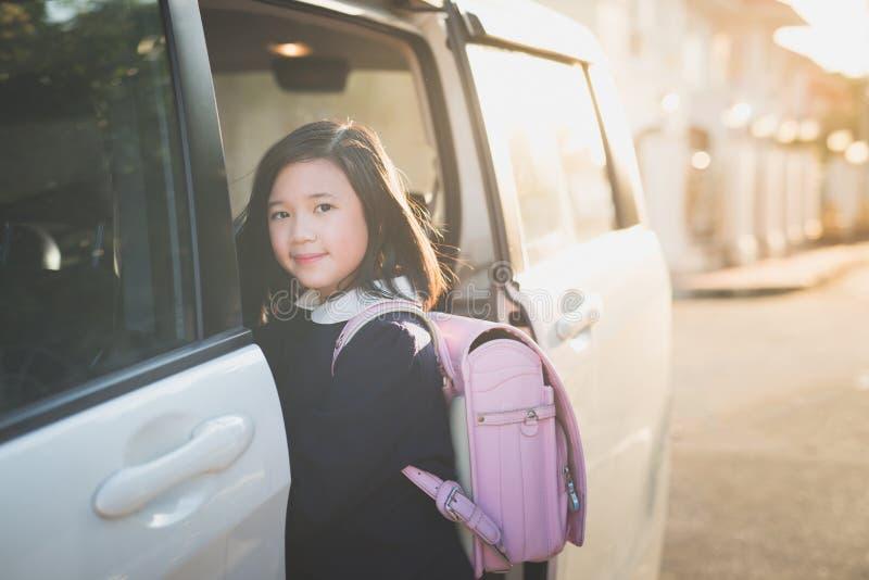 Fille asiatique dans l'uniforme d'étudiant allant à l'école en voiture images stock