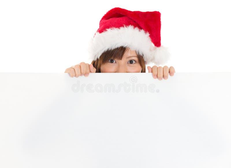 Fille asiatique dans Santa jetant un coup d'oeil au-dessus du panneau de papier de signe image stock