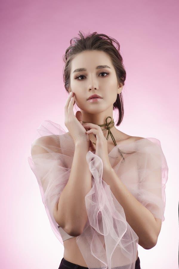 Fille asiatique de beau jeune grand sein avec du charme portant le VE rose photo libre de droits