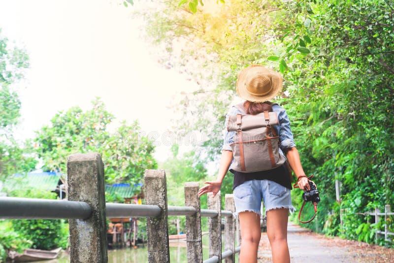 Fille asiatique de hippie avec l'appareil-photo respirant et regardant le passage couvert et le canal tropicaux, voyageur de tour image stock