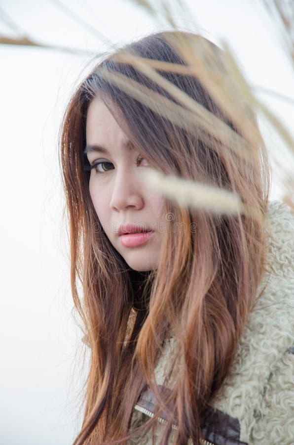 Fille asiatique de longs cheveux dans la robe blanche portant bas de marche de grand chapeau en osier le seul le gisement de fleu photos libres de droits