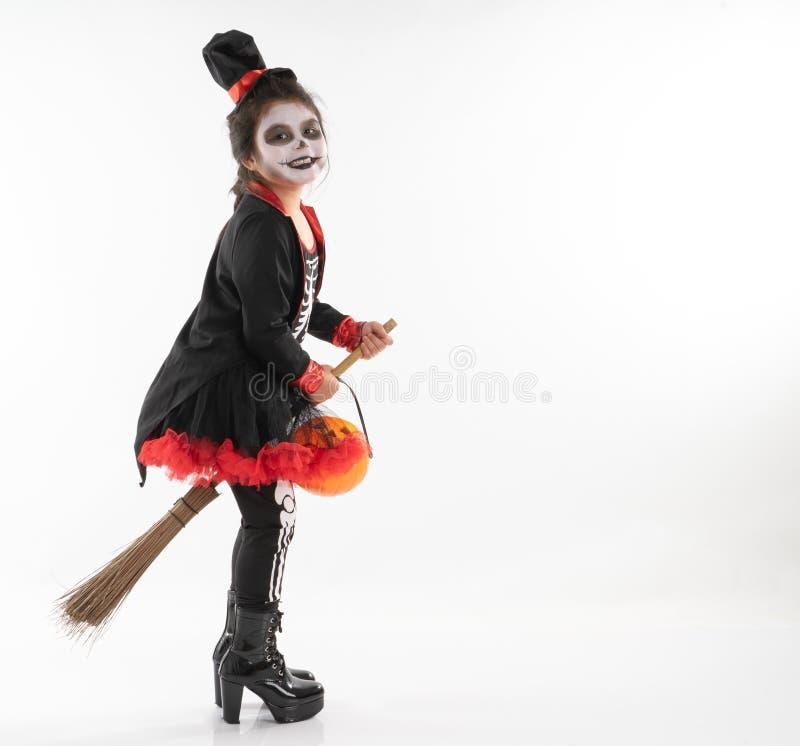 Fille asiatique de portrait dans le costume de Halloween montant le balai avec t image stock