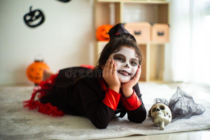 Fille asiatique de portrait petite dans le costume de Halloween souriant au c image stock