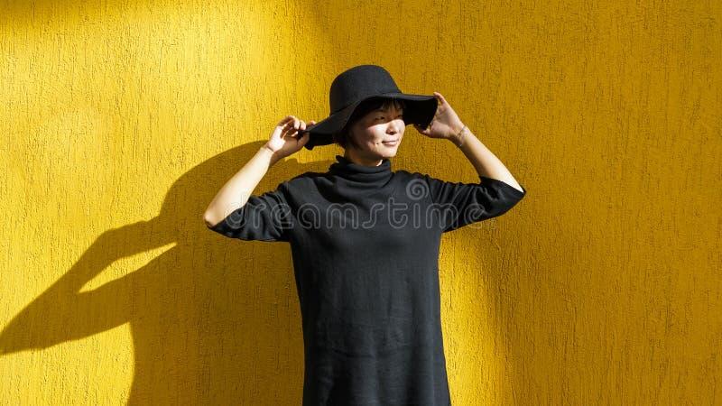 Fille asiatique de sourire avec le chapeau noir et la robe noire image stock