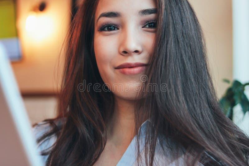 Fille asiatique de sourire de belle brune avec du charme avec le comprimé au café, fin  image stock