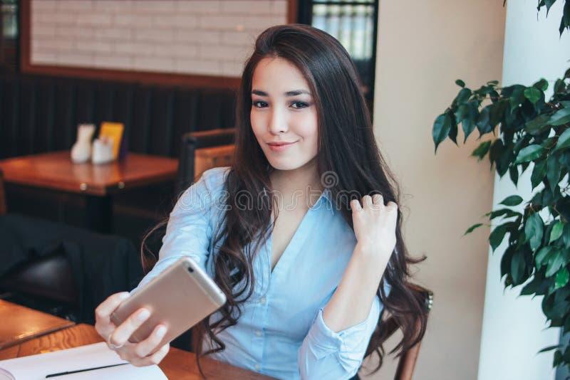 Fille asiatique de sourire de belle brune avec du charme prenant le selfie sur la caméra frontale du smartphone au café photos stock