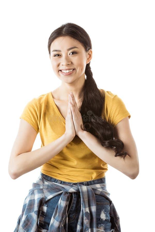Fille asiatique de sourire de jeunes avec le geste traditionnel de salutation image stock