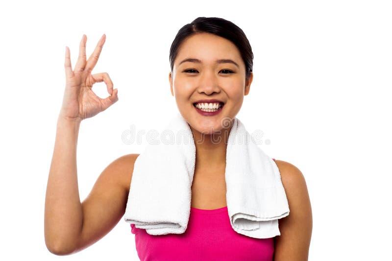Fille asiatique de sourire montrant le signe correct images stock