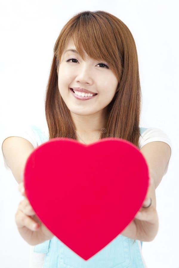Fille asiatique donnant le cadeau rouge de coeur photo stock