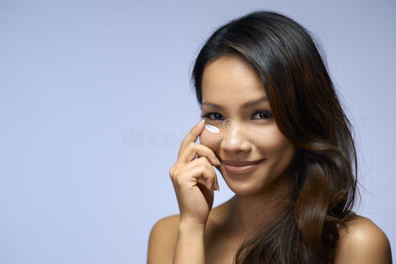 Fille asiatique employant la crème et des cosmétiques de beauté photo stock